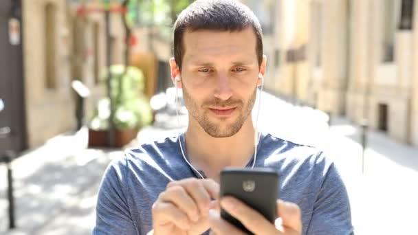 Přední pohled seriózního dospělého muže, který poslouchá kontrolu hudby po telefonu