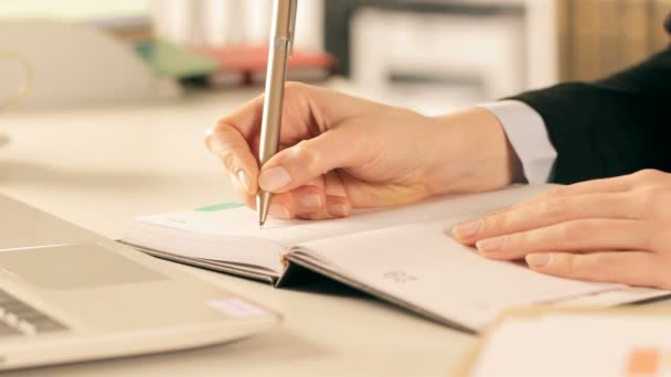 Close up of executive hands writing in paper agenda with a pen on a desk at office
