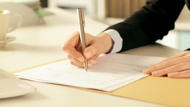 Großaufnahme von Händen, die mit einem Stift auf dem Schreibtisch im Büro ein Häkchen beim Ausfüllen von Formularen machen
