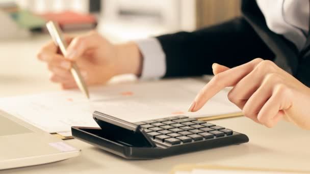 Close up of executive hands doing accounting using calculator comparing document at office
