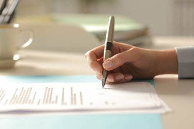 Close up of business woman hands signing contract document on a desk at the office