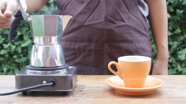 Barista gießt heißen Kaffee aus Mokka-Kanne