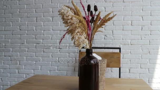 Sušené květy ve váze v bílé kavárně s stůl a židle, skladem video
