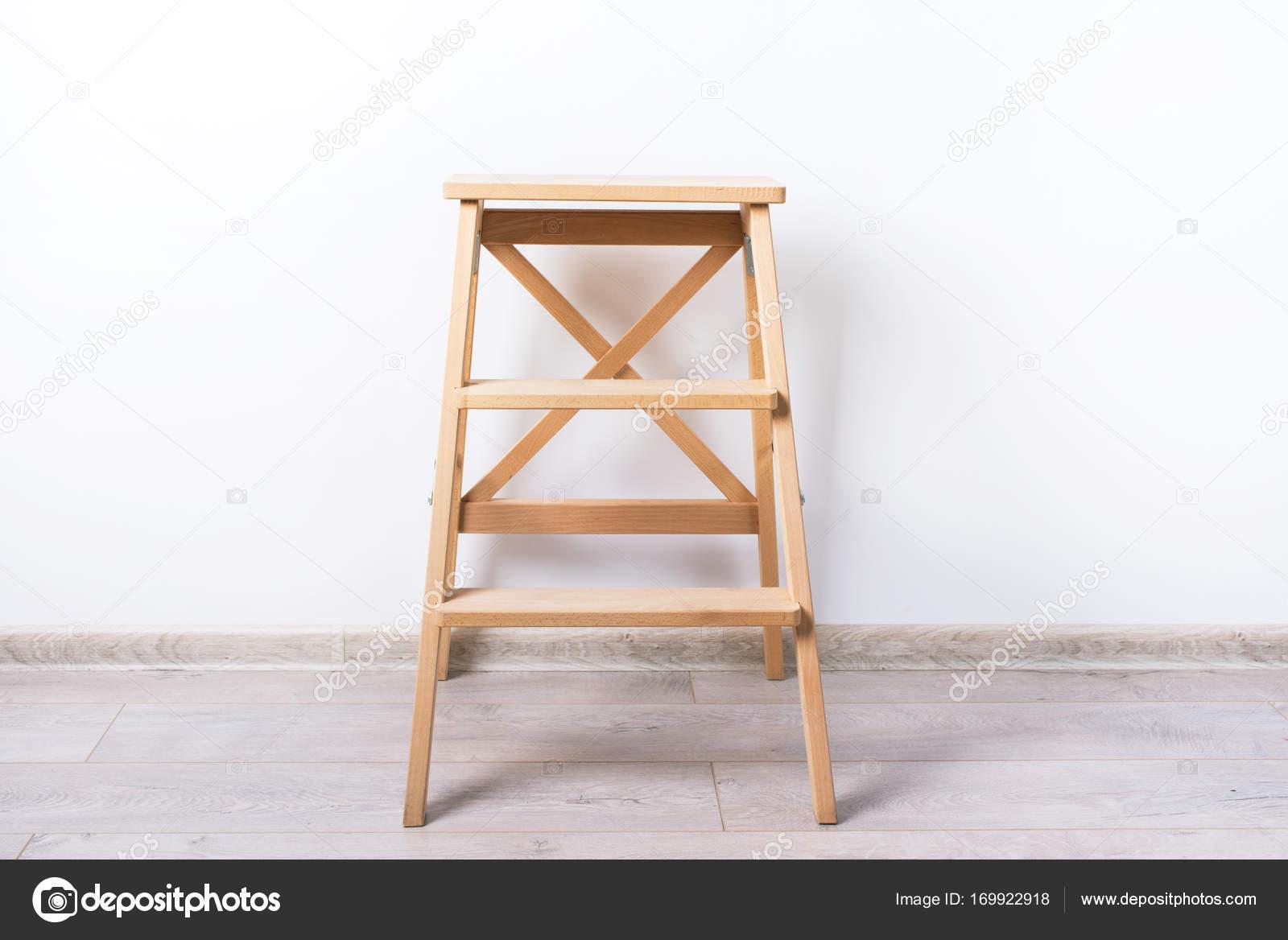 Sedia sgabello in legno luce vicino alla parete bianca u foto