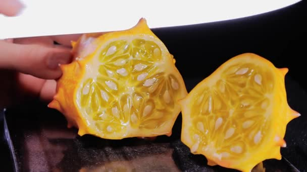 Female hands Cutting African horned melon