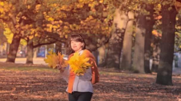 junge Frau spaziert im Park mit einem Strauß gelber Herbstblätter