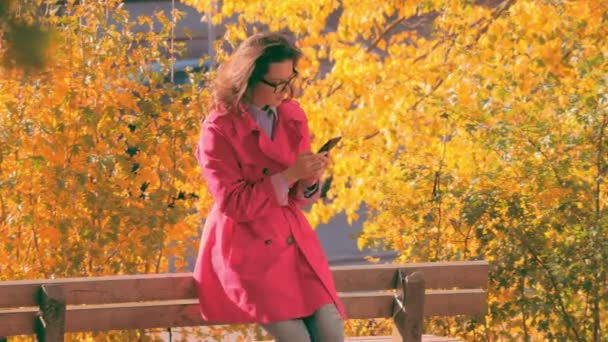Girl texting on the smart phone wearing a red jacket in a autumn park