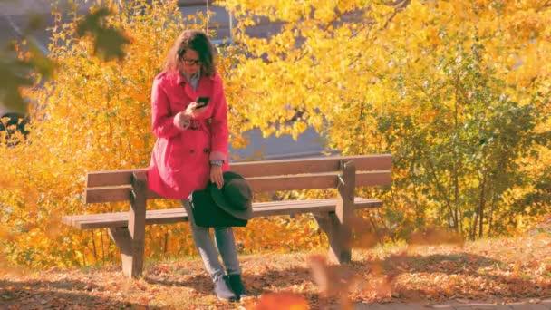 Egy nő laptoppal sms-ezik az okostelefonon egy őszi parkban.