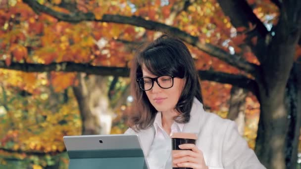 Woman in autumn park drinkink coffee and working with her notebook