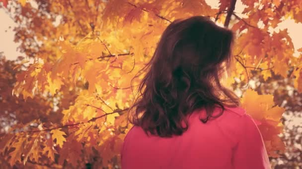 Portrait of cheerful young woman looking at camera with autumn leafs