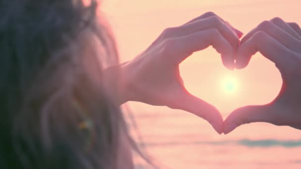 Hands as heart shape with pastel romantic sunset
