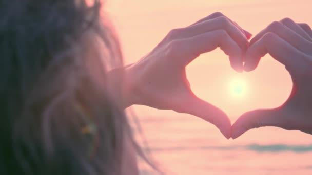 Ruce ve tvaru srdce s pastelově romantickým západem slunce