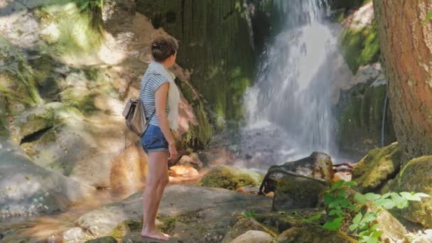 Young woman standing in front of waterfall. Female tourist looking at waterfall.