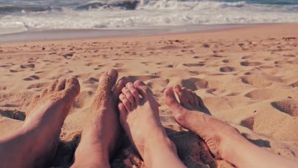 Mužské a ženské nohy přes letní pláž