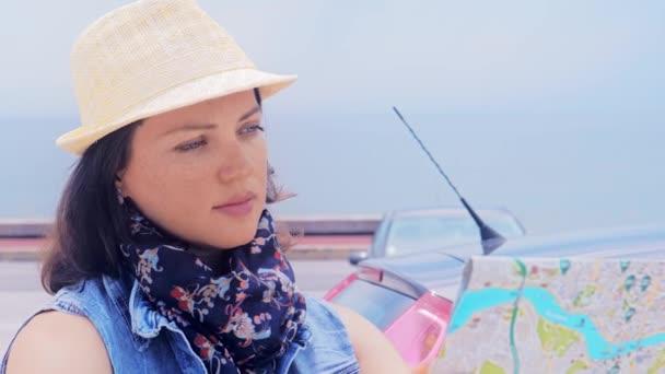 Žena cestovatel v klobouku s mapou v rukou, cestuje autem