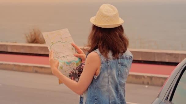 Žena cestovatel v klobouku s batohem a mapou v rukou