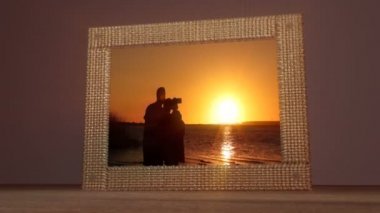 Concept animation of a photograph of an amazing sunset with a young couple and baby taking a selfie against a sunset over a lake. Water cascades from the frame and the photo becomes a moving clip.