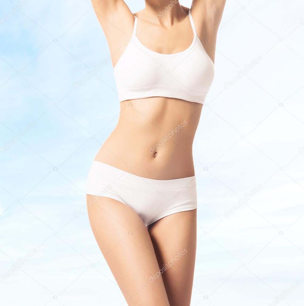 f9954583cffd95 Piękna kobieta szczupły ciało w białe stroje kąpielowe na jasnoniebieskim  tle, przycięte zdjęcie — Zdjęcie od ...