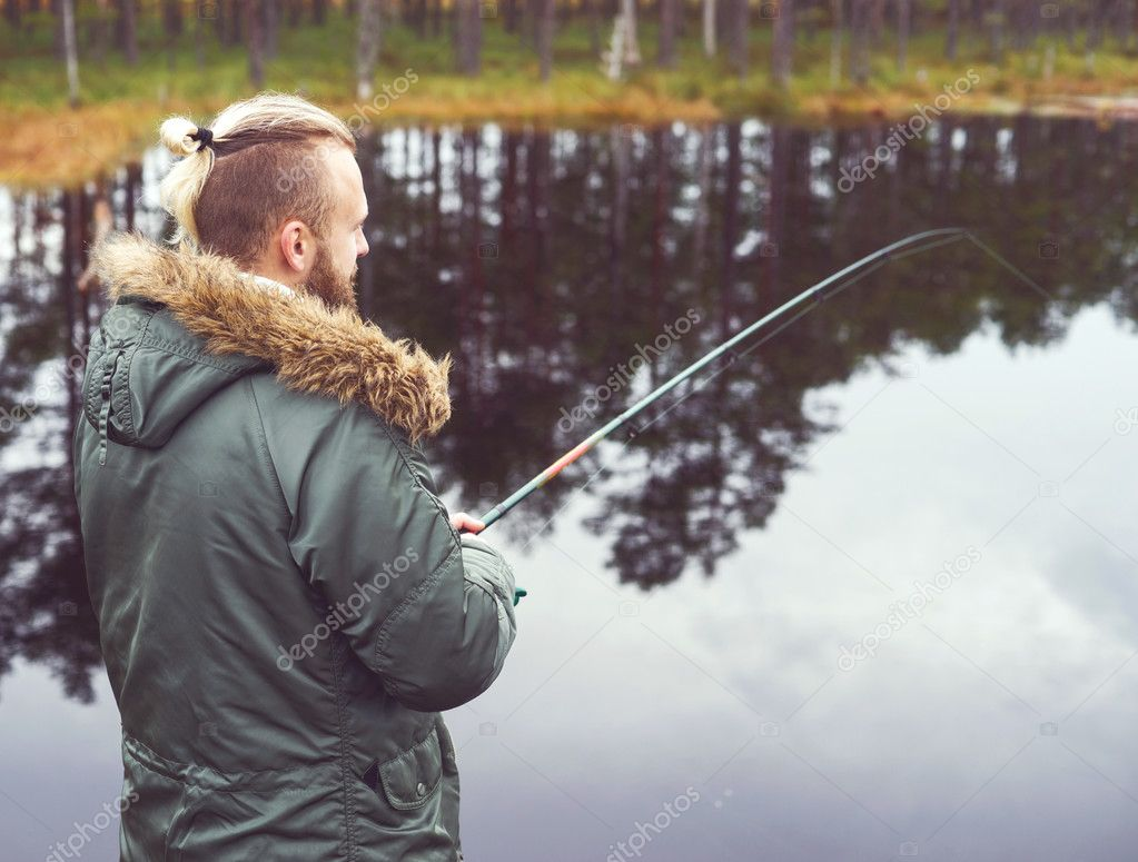 Young man fishing with spinning rod