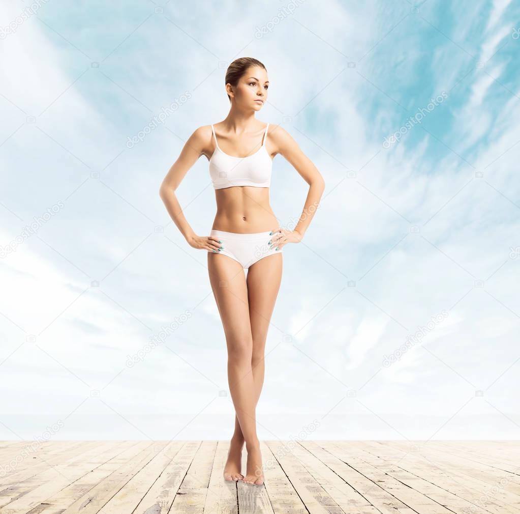 082e03ab3f4294 Młoda brunetka, szczupła kobieta w białe stroje kąpielowe na tle błękitnego  nieba — Zdjęcie od ...