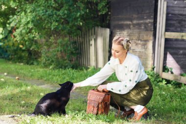 young woman stroking cat on countryside
