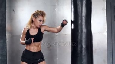 A beautiful and fit woman has a kickboxing training. Sport, health, concept.
