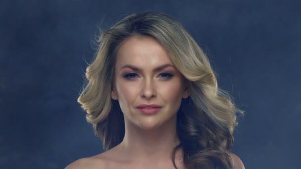 Gyönyörű fiatal nő, egy fúj haját a lassú mozgás.