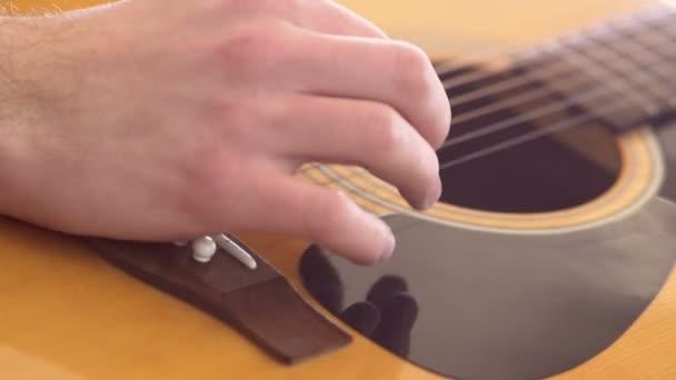 Bokovky chlap hraje akustickou kytaru. Zpomalený pohyb