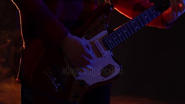 Csípő srác gitáron játszik a színpadon, a füst.