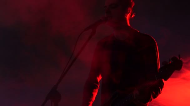 Hipster guy plays bass guitar and sings on stage in smoke. Slow motion. Music, Sound, Band, Concept.