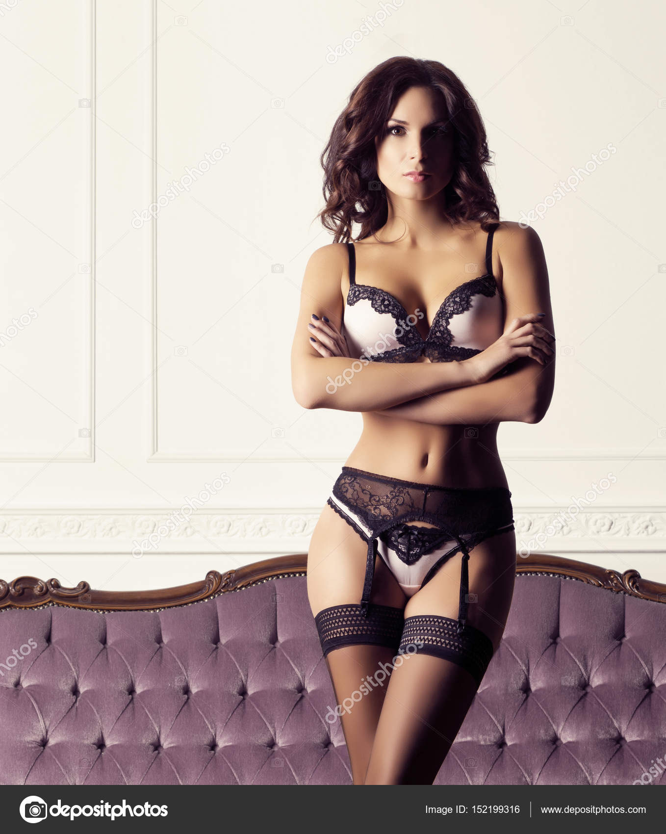 628dc00af Beautiful woman in erotic lingerie posing against magenta retro sofa.  Fashion