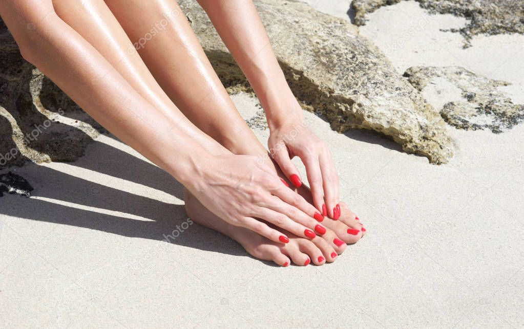 feet and hands with red manicure and pedicure