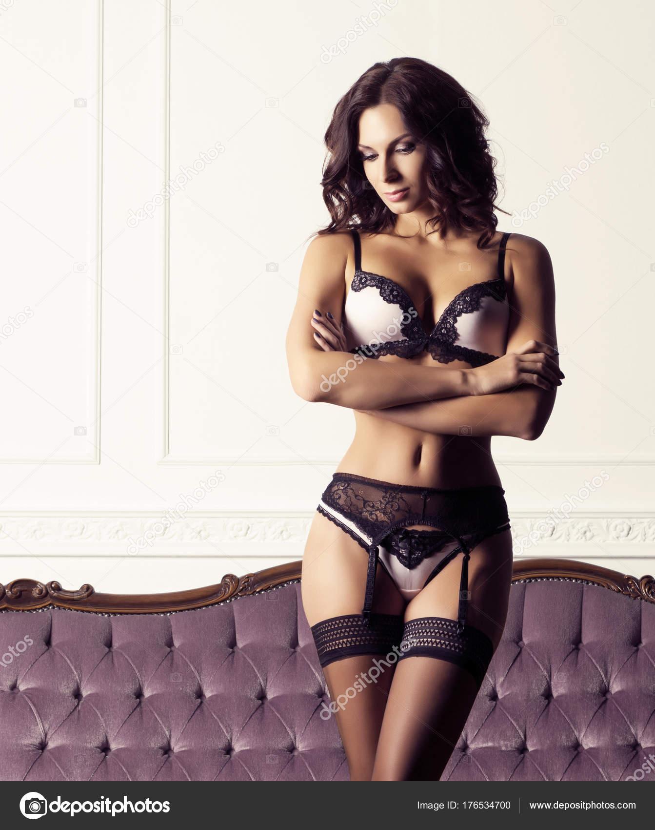 a4065d8f29 Sexy y bella mujer en lencería erótica y las medias posando sobre un sofá  magenta interior