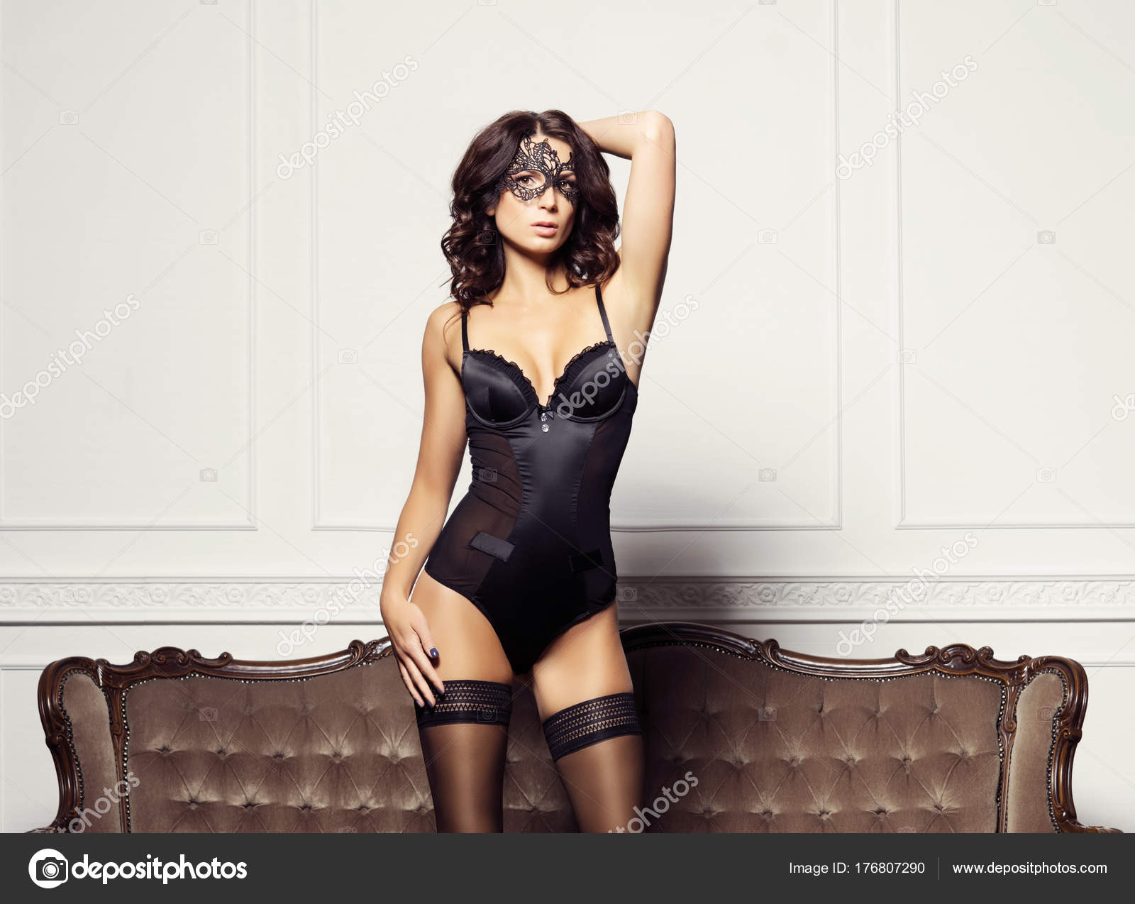 debfb4e90f Sexy y bella mujer en lencería erótica y las medias posando sobre un sofá  marrón en