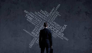 young and confident businessman in black suit standing over dark background with different words. Success, idea, information concept
