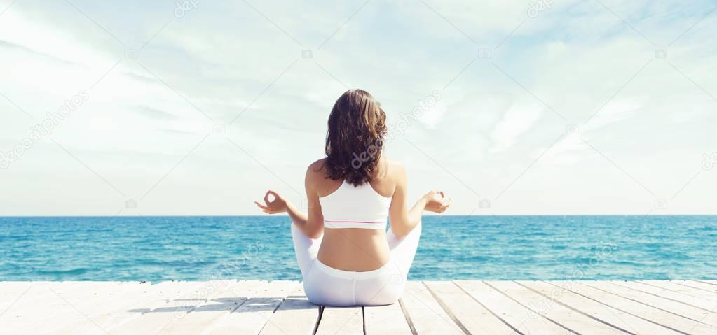beautiful young woman in white sporty clothes meditating on wooden pier on summer. Sea and blue sky background. Yoga, sport, vacation, traveling and freedom concept