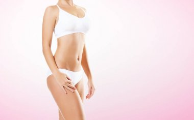 Fit and sporty girl in white underwear. Beautiful and healthy woman posing over magenta background. Sport, fitness, diet, weight loss and healthcare concept.