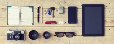 Outfit of a stylish traveler. Set of different objects and equipment: tablet, phone, album, glasses, camera, lenses, gumshoes, knife and watches