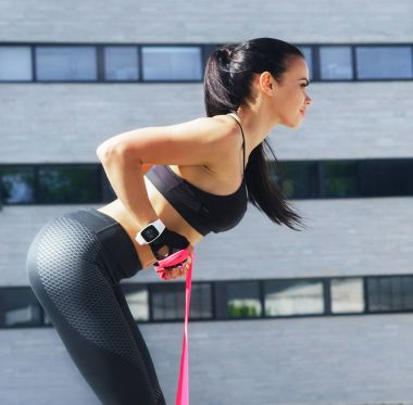 Young and sporty woman training with elastic band outdoor. Resistance training concept.