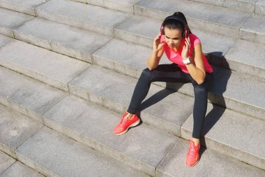 Young, fit and sporty woman preparing for urban jogging. Sport, fitness and healthy lifestyle concept.