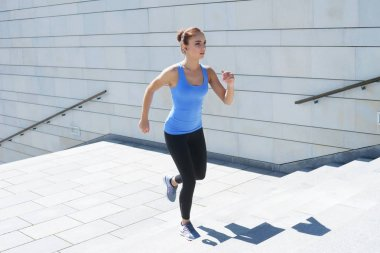 Young, fit and sporty girl running up the stairs. Fitness, sport, urban jogging and healthy lifestyle concept.