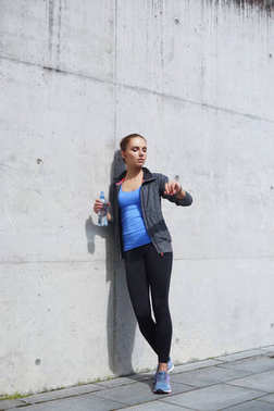 Young, fit and sporty woman standing in front of concrete cement wall. Fitness, sport, urban jogging and healthy lifestyle concept.
