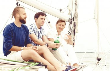 Happy friends sitting together on a deck of a yacht enjoying a good day and having a drink. Summer, holiday concept.
