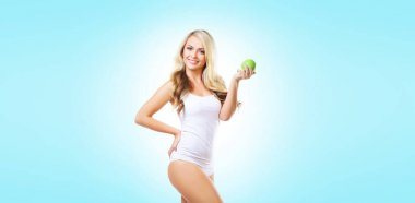 Fit and sporty girl in white underwear. Beautiful and healthy woman eating green apple over cyan background. Sport, fitness, diet, weight loss, nutrition and healthcare concept.