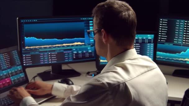 Éjszaka az irodában dolgozó kereskedő munkaállomást és elemzési technológiát használ. Tőzsdepiacok, kriptovaluta, globális üzleti, pénzügyi kereskedelmi és banki koncepció.