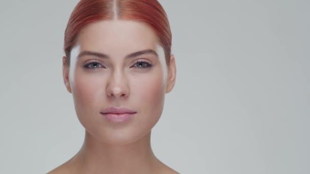 Stúdió portré fiatal, gyönyörű és természetes vörös hajú nő alkalmazó bőrápoló krém. Arcfelvarrás, kozmetikumok és smink koncepció.