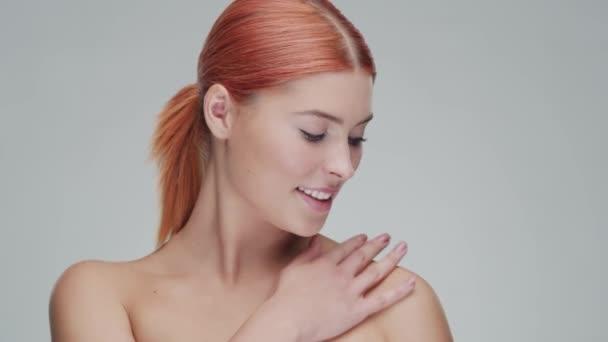 Studio portrét mladé, krásné a přírodní zrzky ženy aplikující krém na péči o pleť. Zvedání obličeje, kosmetika a koncept make-upu.
