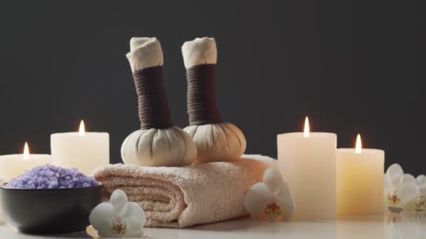 Kompozice lázeňského prostředí. Ručník, svíčky, květiny, kameny a bylinné koule. Koncept masáže, orientální terapie, pohody a meditace.