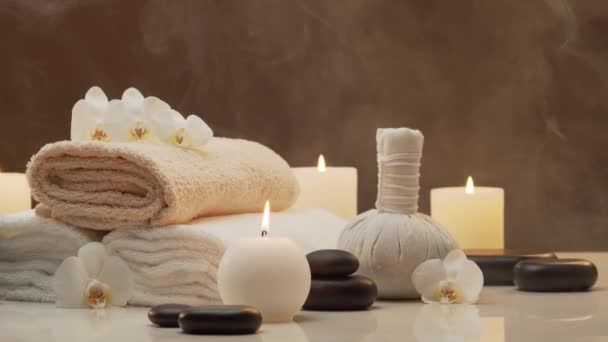 Zusammensetzung der orientalischen Massagebehandlung. Handtuch, Kerzen, Blumen, Steine und Kräuterbälle. Wellness, Meditation, Wohlbefinden und Aromatherapie-Konzept.
