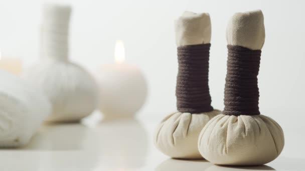 Aromaterápia, keleti masszázs és spa kezelési koncepció. Törölközők, gyertyák, virágok, kövek és gyógynövénygolyók relaxációs összetétele.